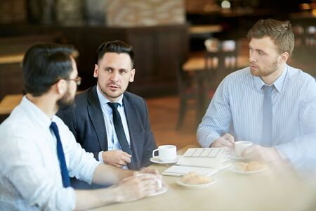formal attire: Three businessmen in formal attire on casual meeting in cafe having coffee and sharing ideas.