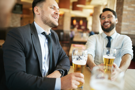 formally: Two formally dressed laughing businessmen chatting and having beer in bar. Stock Photo