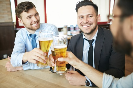 clinking: Three laughing businessmen in formal clothes having beer in bar after work celebrating with clinking glasses