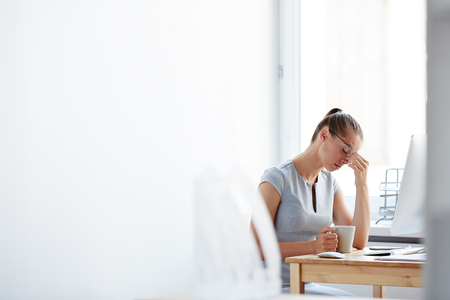 woman in office: Tired young woman sitting at computer desk with cup of coffee touching forehead with her hand, feeling stressed and overworked, copy space to the left