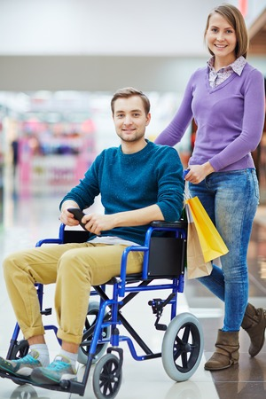 overcoming adversity: Bright colorful image of young smiling man in wheelchair and his wife or girlfriend posing in shopping center looking at camera