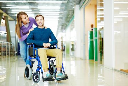 paraplegico: imagen a todo color de la joven pareja, minusválido en silla de ruedas y su novia, disfrutar del tiempo libre en el centro comercial junto