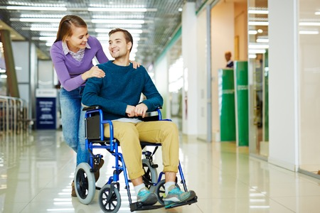 Young couple, woman and physically impaired man in wheelchair, having fun as they stroll in shopping center together dressed in colorful clothes