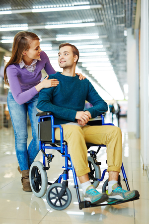 overcoming adversity: Confident young physically impaired man in wheelchair looking at girlfriend holding him from behind as she bends to look in his eyes
