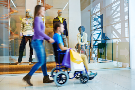 wheeling: Motion image of woman wheeling handicapped man past shopping windows with mannequins display in mall during day of shopping Stock Photo