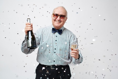 Waist up portrait of smiling well-dressed senior man in sunglasses holding bottle of sparkling wine and full wineglass with confetti falling from above against white background.