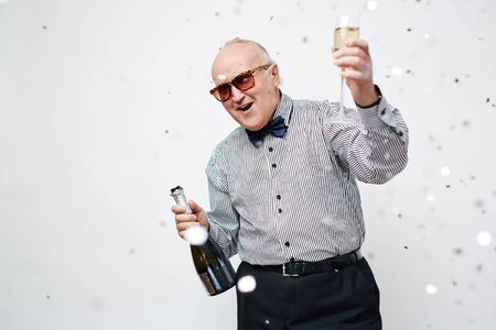 new age: Waist up portrait of senior man in sunglasses dressed in stylish shirt with bowtie having fun with sparkling wine and confetti around him against white background. Stock Photo