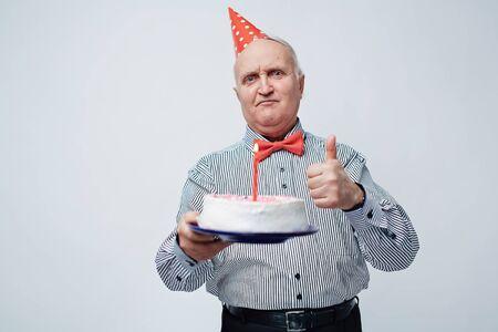 persona de la tercera edad: Cintura para arriba retrato del viejo hombre satisfecho y festivamente vestida en casquillo del cumpleaños que muestra el pulgar hacia arriba y la celebración de la torta con la vela contra el fondo blanco