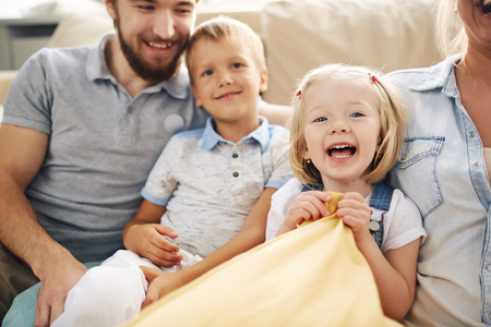 Family of four, father, mother, son and daughter, sitting together on couch in living room,   focus on smiling blonde girl laughing in foreground, tender scene Stock Photo