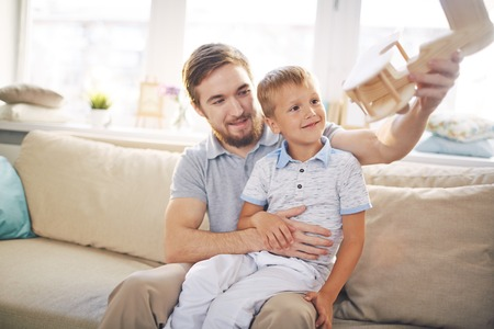 six years: Young man in sunlit living room holding six years old son on knee and showing him wooden model of airplane flying Stock Photo