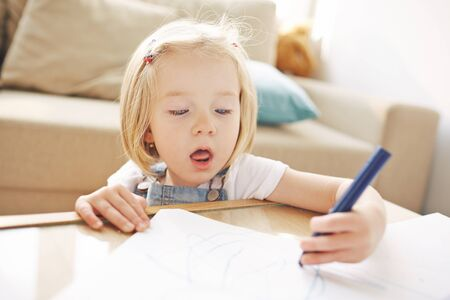 Closeup of cute blonde girl of five or six years busy doodling in living room, she is so concentrated on drawing that her mouth opens Stock Photo