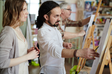grey haired: Male artist dressed in white with ponytail and pencil tucked behind ear showing woman how to sketch with pencil on easel in art studio with painting grey haired man in background. Stock Photo