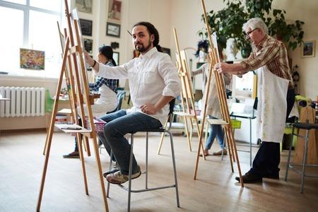 artistas: artista masculino en camisa blanca que se sienta detrás de la pintura de caballete y posando para la cámara en estudio luminoso con un maduro y dos jóvenes estudiantes de sexo femenino en delantales pintan en caballetes atrás.