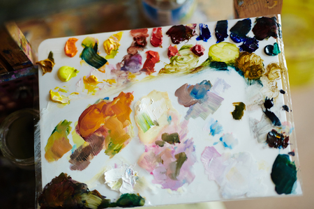 mixing: Top view close up of painting palette covered in colorful and mixed oil paint. Stock Photo