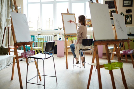 eyeing: Rear view of young woman sitting near window sketching on easel with pencil in brightly lit studio. Stock Photo