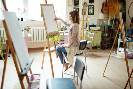 brightly lit: Side view of elegant young female sketching on canvas with pencil in brightly lit studio.