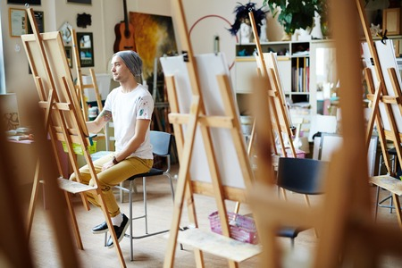 Young man in white shirt covered in paint sitting behind easel sketching on canvas in brightly lit studio.