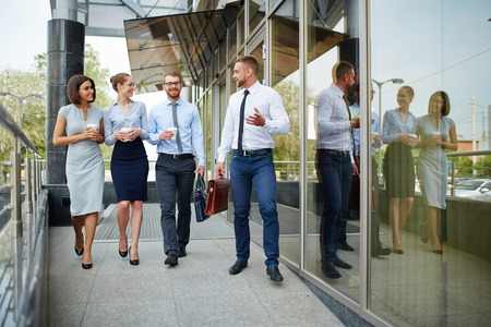 and white collar workers: Group of white collar workers walking along modern building Stock Photo