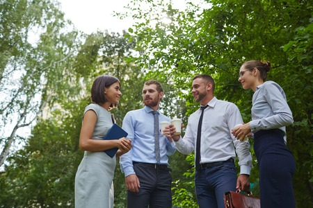 break in: Happy colleagues talking at break in park Stock Photo