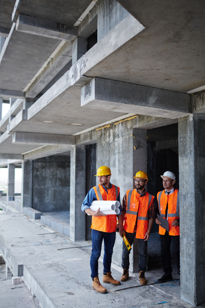 inspectors: Inspectors in helmets and uniform standing by unfinished construction