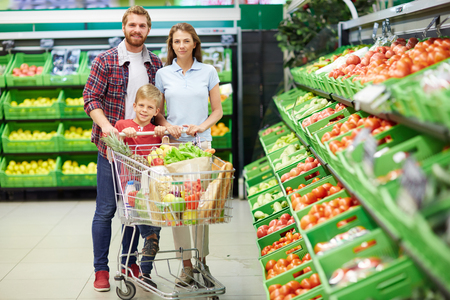 happy families: Happy consumers with push-cart looking at camera in hypermarket