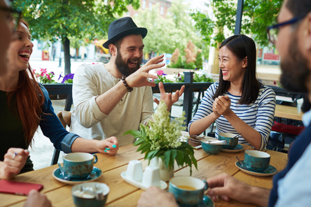 Bearded man in hat telling his friends funny story in cafe