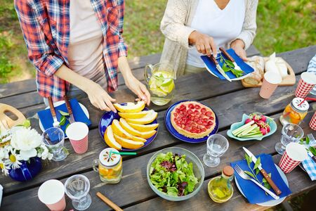 Human hands during preparation of food and serving table for picnic