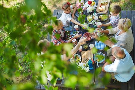 Familieleden verzameld door een diner tafel buiten Stockfoto