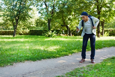 gameplay: Contemporary young man with smartphone playing vr game in park