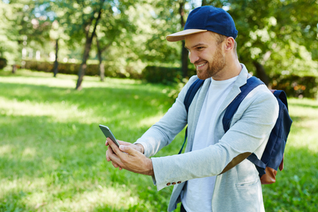 Happy young man looking at his smartphone display outdoors
