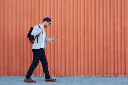rucksack ': Man in casualwear carrying rucksack and playing mobile game Stock Photo