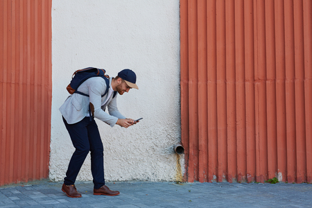 gameplay: Contemporary active man playing popular mobile game in his smartphone outdoors Stock Photo