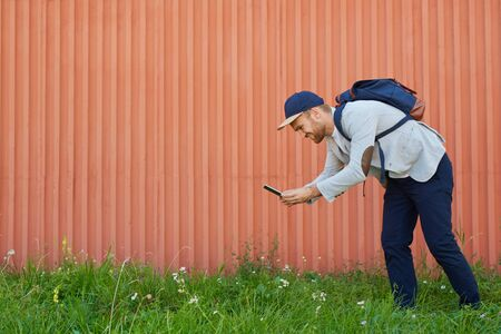 Curious young man with smartphone walking in green grass