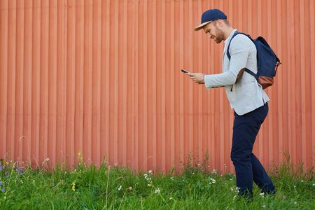 Handsome young man with smartphone moving along wall outdoors