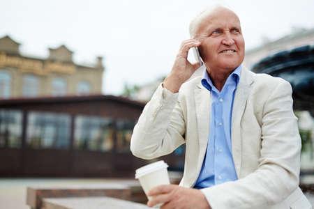 llamando: hombre mayor elegante que llama por el tel�fono m�vil al aire libre Foto de archivo