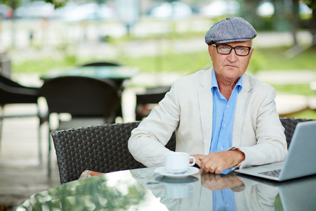 senior men: Serious author looking at camera while sitting in cafe with laptop near by