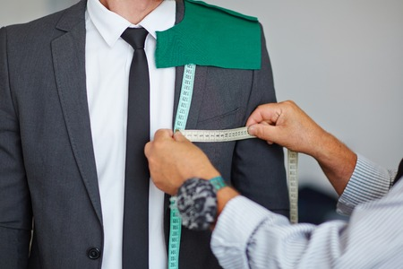 selfemployed: Tailor taking measures from male jacket in workshop