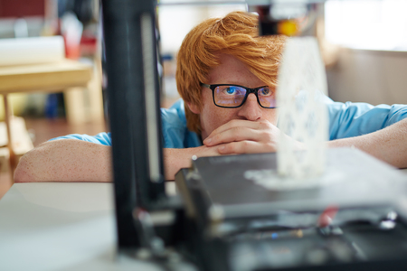 architectural model: Serious designer looking at new architectural model in 3d printer Stock Photo