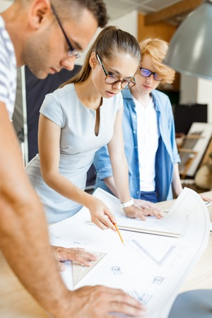 explaining: Female architect explaining details of sketch to co-workers