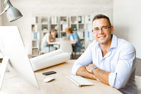 Young specialist sitting at workplace in office Stock Photo