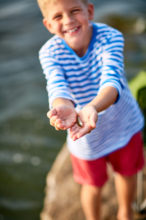 Cute boy showing small fish on his palms