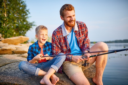 Happy young man and little boy fishing together Stock Photo