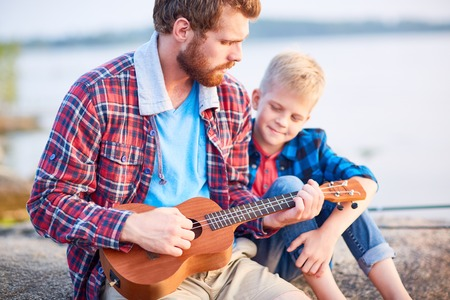 Young man showing his son how to play ukulele
