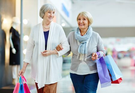 paperbags: Modern aged females with paperbags walking down trade center Stock Photo