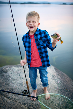 Successful boy with rod showing caught perch