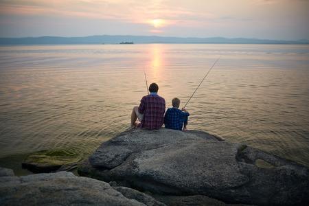 두 명의 어부가 저녁에 호수로 돌에 앉아 스톡 콘텐츠