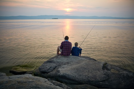Two fishermen sitting on stone by lake in the evening Stock Photo - 61736676