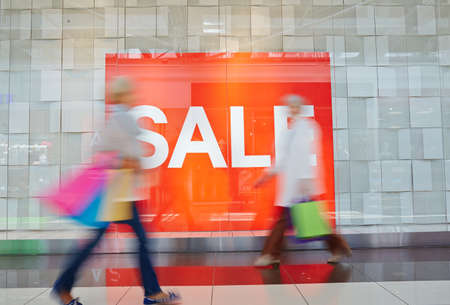 hurrying: Red billboard of sale and hurrying shoppers against it