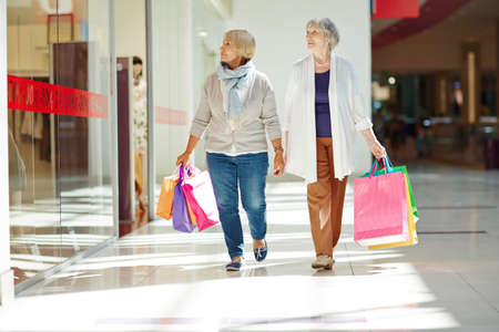 consumers: Two consumers passing by shop window during sale