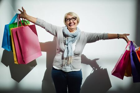 Ecstatic customer with paperbags after successful shopping